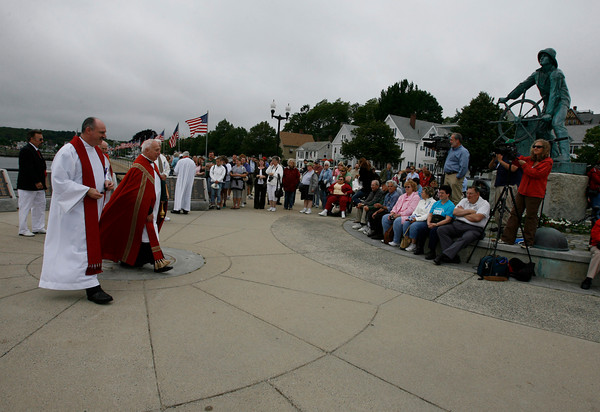 Gloucester: Rev. Timothy Harrison of Holy Family Parish and Father Eugene Alves of Our Lady of Good Voyage Church pass by the Fishermen's Statue after blessing the fleet yesterday afternoon. Photo by Kate Glass/Gloucester Daily Times Sunday, June 28, 2009