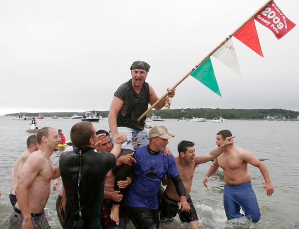 Gloucester: Stew McGillivray cheers as he is carried to shore after winning the greasy pole contest on Sunday. McGillivray also won the Sunday contest last year. Photo by Kate Glass/Gloucester Daily Times Sunday, June 28, 2009