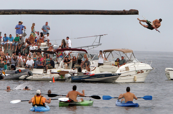 Gloucester: Jason Favaloro grabs the flag at the end of the greasy pole Friday night. Mary Muckenhoupt/Gloucester Daily Times