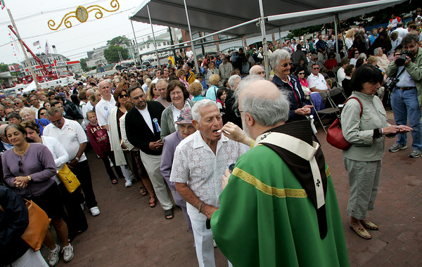 Gloucester: Tony Testaverde receives communion from Cardinal Sean O'Malley at Fiesta mass Sunday at St. Peter's Square. Mary Muckenhoupt/Gloucester Daily Times