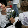 Gloucester: Josephine Russo accepts a rose from her son Salvatore, right, while holding her baby John Matteo in front of St. Ann Church Sunday. This years Fiesta was held in memory of her husband Matteo and father John who were lost at sea on their fishing vessel The Patriot in January. Mary Muckenhoupt/Gloucester Daily Times