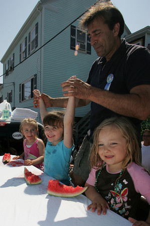 Gloucester: Joe Palmisano announces the winner of the little girls watermelon eating contest at Beach Court Saturday afternoon. Devosha Pearce, 5, won against Madison Moseley, left and Amelia Fontaine. Mary Muckenhoupt/Gloucester Daily Times
