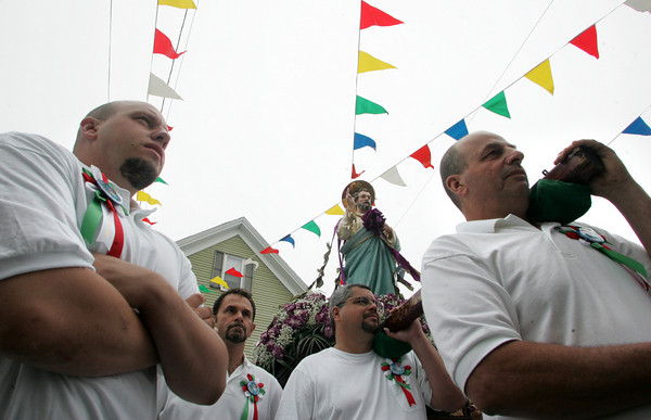 Gloucester: From left, Adam Orlando, John Scola, Peter Frontiero and Joe Orlando stand with the St. Peter statue in front of the Mother of Grace Club on Washington Street during the Fiesta procession Sunday. Mary Muckenhoupt/Gloucester Daily Times