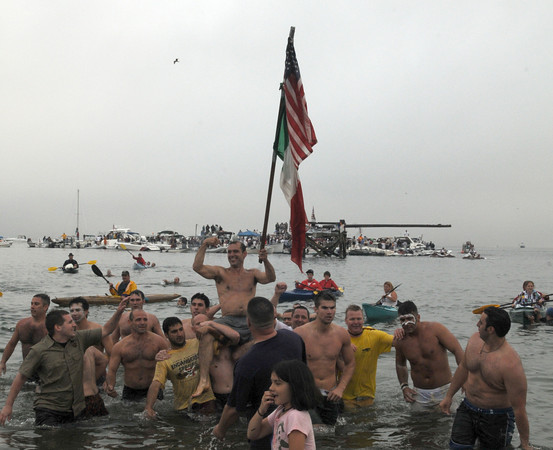 Gloucester: Joe Stelline is carried by other walkers on to Pavilion Beach after taking down the flag in Saturdays Greasy Pole contest.Desi Smith Photo/Gloucester Daily Times. June 27,2009.