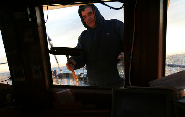 Gloucester: Joe Orlando cleans salt spray from the windows as the sun rises. Photo by Kate Glass/Gloucester Daily Times