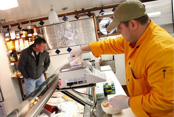 Gloucester: Jeff DiMeo weighs some cod cheeks for Dan D'Entremont at Intershell in Gloucester Friday afternoon. Mary Muckenhoupt/Gloucester Daily Times
