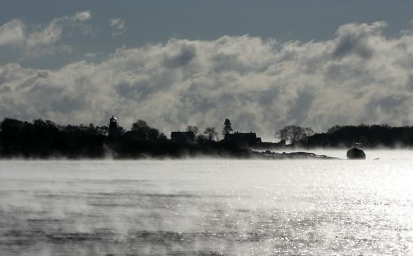 KEN YUSZKUS/Staff photo.  Sea smoke rises off Gloucester harbor Thursday morning.     01/08/15