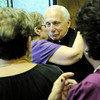 PAUL BILODEAU/Staff photo. Rev. Eugene Alves is hugged by a group of parishioners during a party for the retired priest at the Our Lady of Good Voyage Parish Hall last night.