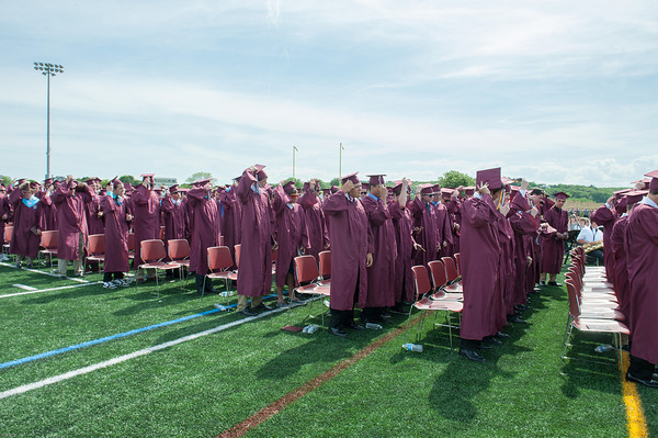 DESI SMITH/Staff photo. The boys of the Class of 2014 move their tassels to the right bring the graduation to close,Sunday afternoon at Gloucester High School Graduation ceremoies, at New Balance Track and Field at Newell Stadium.  June 8,2014