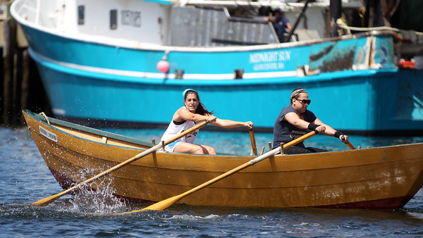 Amanda Palazzola, left, and Lindsey Rogers, paddle hard at the start of the Women's Division dory race on Saturday morning. DAVID LE/Staff photo. 6/21/14.