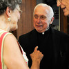 PAUL BILODEAU/Staff photo. Rev. Eugene Alves talks with parishioners Joan and Fred Bishop of Gloucester during a party for the retired priest at the Our Lady of Good Voyage Parish Hall last night.