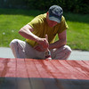 DESI SMITH/Staff photo.  Craig Harkless of Craig Harkless Painting in Essex, puts the final stroke of paint on the Woodman's Retail Stores deck Monday morning.    June 3,2014