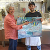 """GAIL MCCARTHY/Staff photo<br /> Brad Curcuru, right, longtime employee of the Steve Connolly Seafood Company, receives a print from artist Mary Ann Wenniger. Brad is the figure depicted in the right side of the print, where Mary Ann is pointing. The print is from the artist's """"People at Work and Play"""" series."""