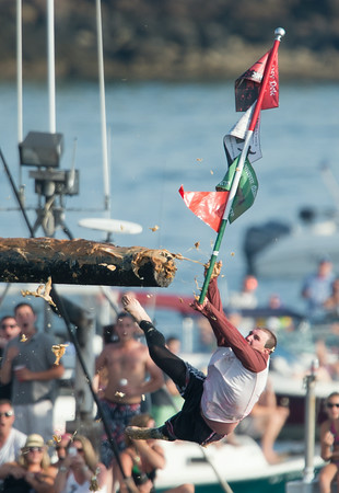 DESI SMITH/Staff photo.  Kyle Barry takes down the flag and lot's of grease, in the thrid round in Saturday's Greasy Pole contest off Pavilion Beach.<br />   June 27,2014