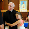 PAUL BILODEAU/Staff photo. Rev. Eugene Alves gets a hug from his great niece Erin McCarthy, 9, of Gloucester during a party for the retired priest at the Our Lady of Good Voyage Parish Hall last night.