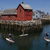 "MIKE SPRINGER/Staff photo<br /> Guide Matthew Rostkowski, center, of North Shore Kayak Outdoor Center in Rockport, takes Maureen McNamara, left, and Michael McNamara, both of Andover, past the famous ""Motif No. 1"" fishing shack during a paddleboarding tour of Rockport Harbor on Monday."