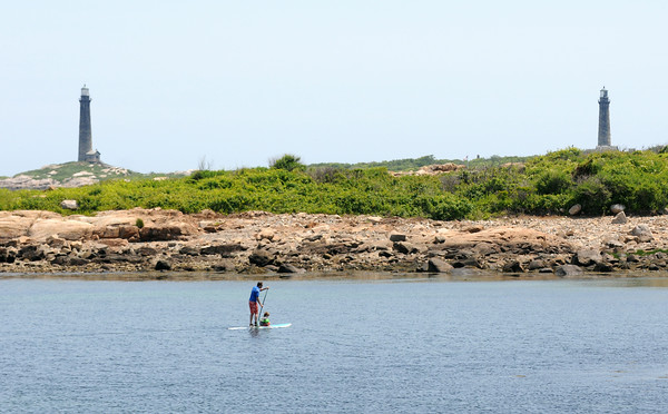 PAUL BILODEAU/Staff photo. A stand up paddle boarder crosses Loblolly Cove in Rockport on a beautiful early Summer day on Tuesday.