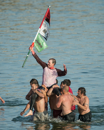 DESI SMITH/Staff photo.  Kyle Barry is carried to shore by other contestants in Saturday's Greasy Pole contest off Pavilion Beach.<br />   June 27,2014