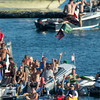 DESI SMITH/Staff photo.  A crowd of spectators cheer as Jack Russ rips down the flag, in Friday's Greasy Pole contest off Pavilion Beach.<br />   June 27,2014
