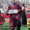 DESI SMITH/Staff photo.    Matthew Lane shows off his deploma as he heads back to his seat Sunday afternoon at Gloucester High School Graduation Ceremoies, at New Balance Track and Field at Newell Stadium.  June 8,2014