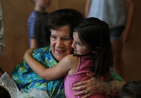 MIKE SPRINGER/Staff photo<br /> Connie Brown receives a hug from second grader Naia Zachareas at the conclusion of a tribute to Brown held during an all-school assembly Wednesday at Manchester Memorial Elementary School in Manchester. The 91-year-old Brown is retiring after 14 years of service as a volunteer reading helper at the school.