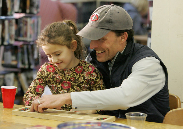 Essex: Joel Laino and his daughter Amelia, 6, play a game of Mancala at TOHP Burnham Library's Game Day Friday afternoon.  Amelai's sister Annalia had also been playing with them but left to play agame of Checkers with her friend. Mary Muckenhoupt/Gloucester Daily Times