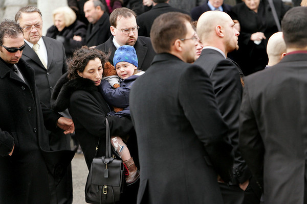 Gloucester: Josephine Russo, the widow of Matteo Russo, holds her son Salvatore, 3, as they leave the funeral service at St. Ann Church Thursday morning.  Mary Muckenhoupt/Gloucester Daily Times