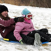 Gloucester: Ann Marie Hamel, 14, and her sister Andrea, 8, make their way down a hill at Stage Fort Park Friday. Most of the snow had blown away but that didn't stop kids from taking advantage of their last days of school vacation with an afternoon of sledding. Mary Muckenhoupt/Gloucester Daily Times