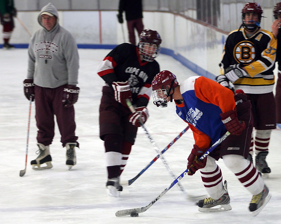 Gloucester: Connor Cranston, front, works on a defensive drill as head coach Don Lowe, left, and teammates Vincenzo Terranova, center, and Brett Cahill, right, look on during practice yesterday. The Fishermen have shifted to more of a defensive-minded team this season. Photo by Kate Glass/Gloucester Daily Times Tuesday, January 20, 2009