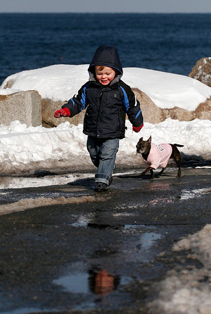 Alexander Bajoras, 22 months, of Gloucester walks with Miss Roxy of Rockport around the end of Bearskin Neck while out with his grandparents, George and Jeannette Bajoras on Wednesday afternoon. Photo by Kate Glass/Gloucester Daily Times Wednesday, January 21, 2009