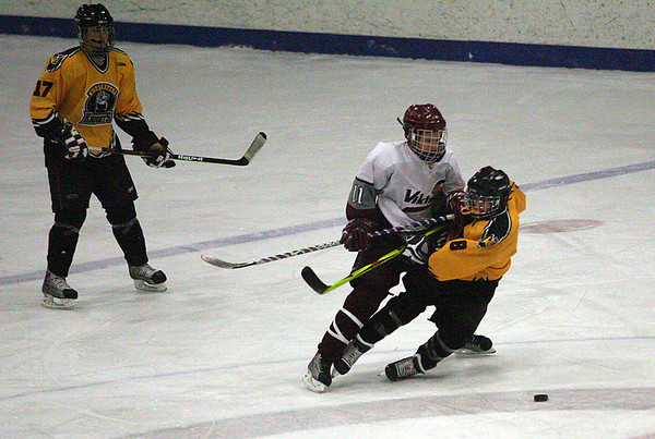 Rockport: Rockport's Brendan Douglass knocks Northeast's Mike Cross down at center ice as Bobby Trousant looks on during the Vikings' 3-2 win last night. Photo by Kate Glass/Gloucester Daily Times