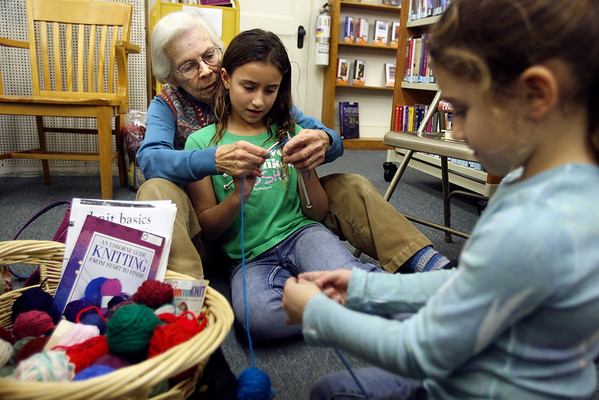 """Essex: Connie Perrigo helps Annalia Laino, 8, with her knitting technique as Laino's sister, Amelia, 5, picks a yarn at the TOHP Burnham Library in Essex on Wednesday. The library hosts """"Learn to Knit"""" every Wednesday from 3 to 5. Photo by Kate Glass/Gloucester Daily Times Wednesday, January 7, 2009"""