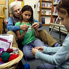 "Essex: Connie Perrigo helps Annalia Laino, 8, with her knitting technique as Laino's sister, Amelia, 5, picks a yarn at the TOHP Burnham Library in Essex on Wednesday. The library hosts ""Learn to Knit"" every Wednesday from 3 to 5. Photo by Kate Glass/Gloucester Daily Times Wednesday, January 7, 2009"