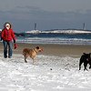 Gloucester: Sheryl Smith of Gloucester walks her dogs Kona, left, and Hula, right, at Good Harbor Beach yesterday afternoon. Smith says she and the dogs are at the beach almost every day because they love to run and it helps them sleep well at night. Photo by Kate Glass/Gloucester Daily Times Wednesday, January 21, 2009