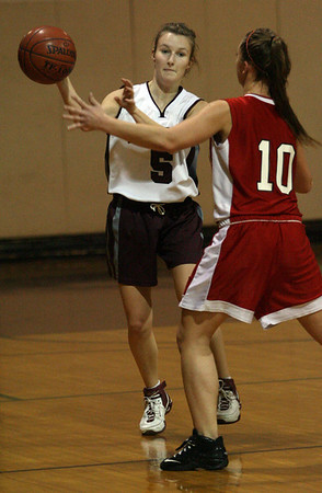 Rockport: Rockport's Hannah Evans passes the ball over Amesbury's Gabby Magnifico during their game at Rockport last night. Photo by Kate Glass/Gloucester Daily Times Monday, January 12, 2009