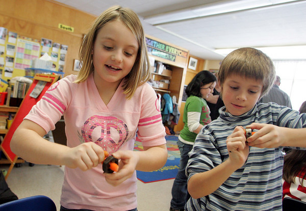 Essex: Summer Burroughs and Liam Hemeon push baby carrots through a carrot screw which shaves the carrot to make it look like a screw in Andrew Burnett's third grade classroom Wednesday afternoon.  The carrot screw station was just one of the fun science activities Johnny Juniper of High Touch High Tech of Boston had set up in the classroom for the kids to do.  They also made levels and were shown how to make a tornado using two soda bottles and some colored water.  Mary Muckenhoupt/Gloucester Daily Times