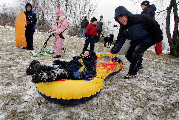 Gloucester: Tom Braden of Gloucester pushes his grandson Sabien, 3, down the hill at Stage Fort Park Friday afternoon.  Many kids came to enjoy a day of sledding despite the fact that much of the snow had blown away. Mary Muckenhoupt/Gloucester Daily Times.