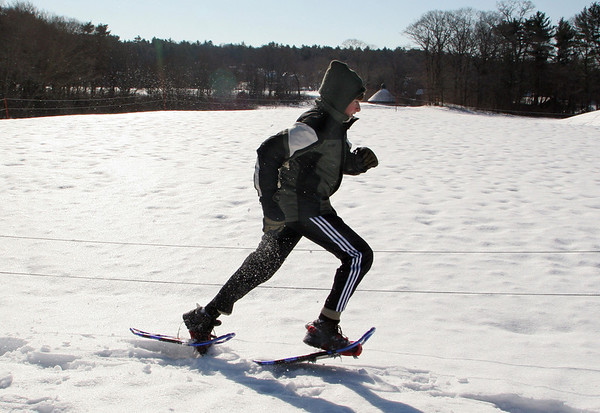 Manchester: Brady Winn runs through the snow while snowshoeing with his classmates Thursday morning.  Eric Magers takes his eighth grade project adventure class out snowshoeing around the Essex County Club golf as long as there's snow on the ground to get the kids outdoors. Mary Muckenhoupt/Gloucester Daily Times