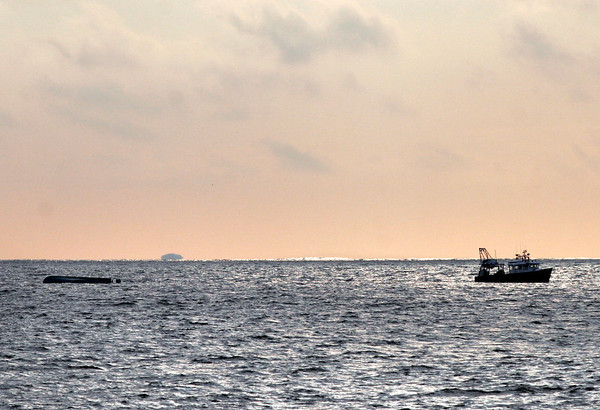 Gloucester: The Providenza, a 38-foot fiberglass clam shell boat, is towed into Gloucester Harbor after it overturned near the Eastern Point breakwater yesterday morning. The two men on board were rescued by Roger Brisson, who was departing on a fishing trip. Photo by Kate Glass/Gloucester Daily Times Monday, January 19, 2009