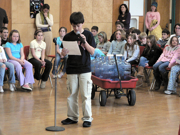 ,Essex: Evan Pennoyer, a forth grader at Essex Elementary School speaks about the hero that his grade selected to present at school meeting Thursday afternoon. The hero his class chose was Ted Agoglia who founded The First Response Team, a group that responds to areas impacted by natural disasters.  Robert Cann/Gloucester Daily Times.