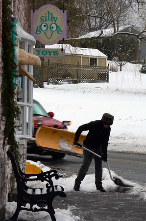 """Essex: Diane Robinson, owner of Silly Goose Toys, clears snow and slush away from the front of her shop yesterday morning. """"I've been splashed a couple of times already,"""" she said, adding, """"It's winter fun."""" Photo by Robert Cann/Gloucester Daily Times Wednesday, January 7, 2008"""