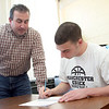 Manchester: Manchester Essex senior Pat Orlando signs his letter of intent to go play football at St. Anselm next fall with hs coach Mike Athanas by his side Wednesday afternoon. Mary Muckenhoupt/Gloucester Daily Times