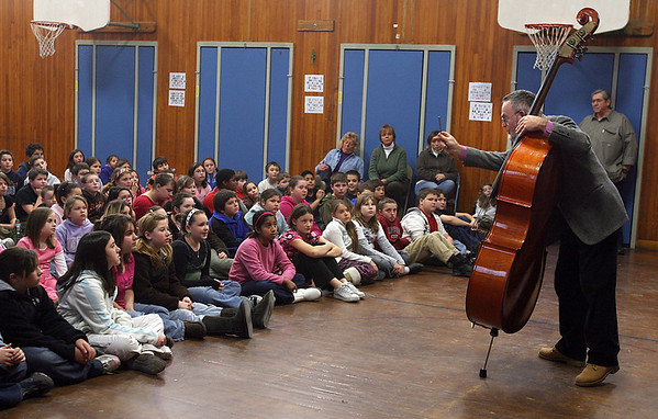 Gloucester: John Stewart, a bass player in the Cape Ann Symphony, shows students at Veterans Memorial School how he tunes his instrument yesterday morning. Members of the symphony are visiting all the area elementary schools in preparation for their premiere of Katy and the Big Snow. They will perform the show for Cape Ann students on January 23rd and then the premiere at the Fuller Auditorium on January 24th at 2pm. Photo by Kate Glass/Gloucester Daily Times Wednesday, January 14, 2009