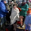 Gloucester: Julian Murry-Brown, 9, of Gloucester tries to stay warm in his towel as his parents get his dry clothes ready after Julian participated in the annual Rocky Neck Plunge at Oak Cove Beach Thursday morning.  Anyone who wanted to swim or just wanted to watch gathered at Sailor Stan's on Rocky Neck before parading down to the beach for the ceremonial swim.  Also pictured is Julian's sister Iona, right. Mary Muckenhoupt/Gloucester Daily Times