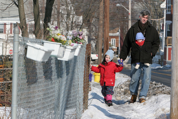 Gloucester: Geoff Deckebach walks down East Main Street with his daughters Frieda Davis, 7 months, and Pilar Davis, 4, while walking home from the playground Friday afternoon. Deckebach says he can't wait for a winter thaw to clear up all the icy sidewalks. Mary Muckenhoupt/Gloucester Daily Times
