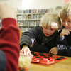 Essex: Luke Smith, 5, makes a move as his brother, Noah, 9, right, helps with Luke's stategie while playing Thomas Ambrose in Checkers during Game Day at the TOHP Burnham Library Friday afternoon.  Various games were placed out including Battleship, Scrabble and Pictureka for kids to drop by and play. Mary Muckenhoupt/Gloucester Daily Times