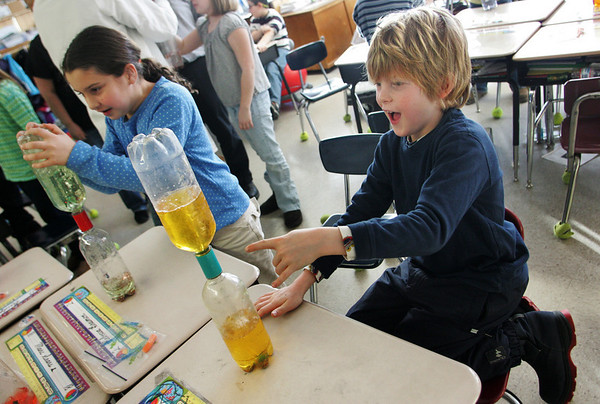 Essex:  Paul DiFluri watches a tornado form in his tornado tube in Andrew Burnett's third grade classroom at Essex Elementary School Wednesday afternoon.  Jupiter Jonny from High Touch High Tech of Boston came to the  school to show the kids fun science projects like how to make a tornado with two soda bottles as well as making a level. Also pictured is Rebecca Braimon, left.  Mary Muckenhoupt/Gloucester Daily Times