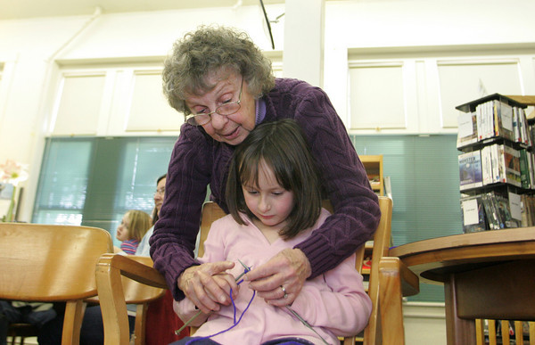 Essex: Cindy Cameron helps Maxine Hickey, 7, learn to knit as the TOHP Burnham Library offers knitting lessons Wednesday afternoon.  Mary Muckenhoupt/Gloucester Daily Times
