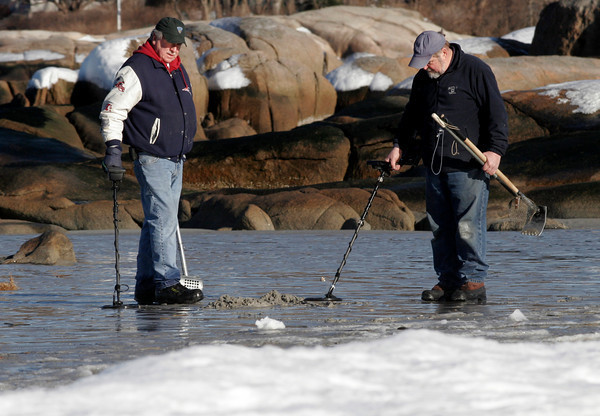 Gloucester: Larry Corcoran, left, and Mike Cashman search for treasures on Wingaersheek Beach yesterday afternoon. The two found several coins and a buried lobster trap. Photo by Kate Glass/Gloucester Daily Times