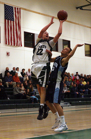 Manchester: Manchester Essex's Joe Mussachia leaps above Wilmington's Mike Murphy during their game last night. Mussachia scored 26 points, including his 1,000th career point during the Hornets' win. Photo by Kate Glass/Gloucester Daily Times